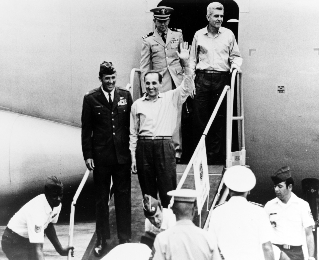 Two of the returned prisoners of war step from the second U.S. Air Force C-141 to leave Hanoi, at Clark Air Force Base, Philippine Islands, in February 1973. They are: Colonel Robinson Risner, USAF (waving), and Captain James Stockdale, USN. Their escorts are Major Leroy W. Thornal, USAF, and Lieutenant Commander Elman J. Parrie, USN.