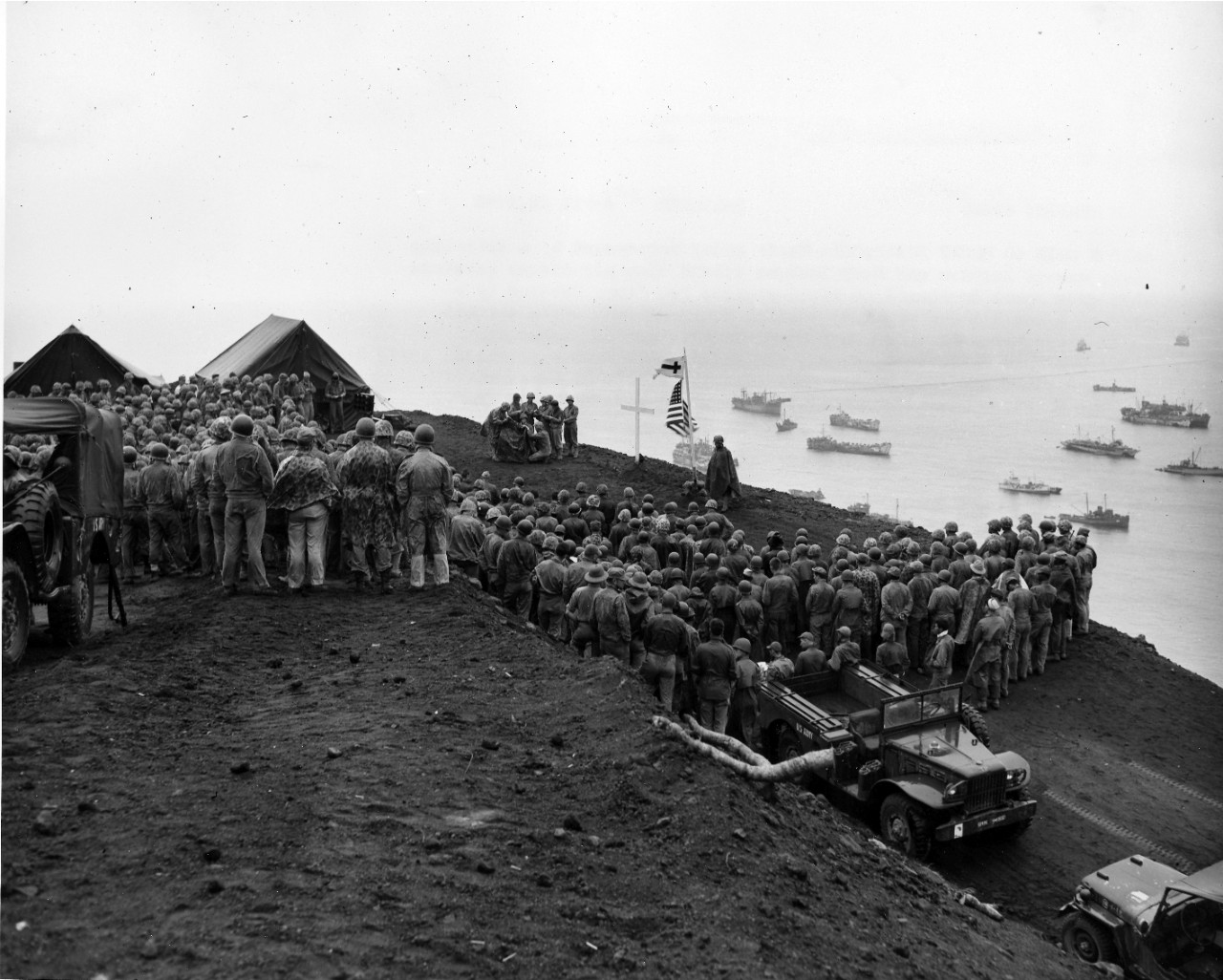 <p>Their ardor undampened by a drizzling rain, Marines and Navy Seabees attend open-air divine services atop Mount Suribachi on blood-stained Iwo Jima. Covered by a poncho, a small organ provides musical accompaniment while a small choir sings hymns. Even as Chaplain Alvo Martin conducted these Easter services, on 1 April, fellow Marines and Army troops were swarming ashore on Okinawa, hundreds of miles away.</p>
