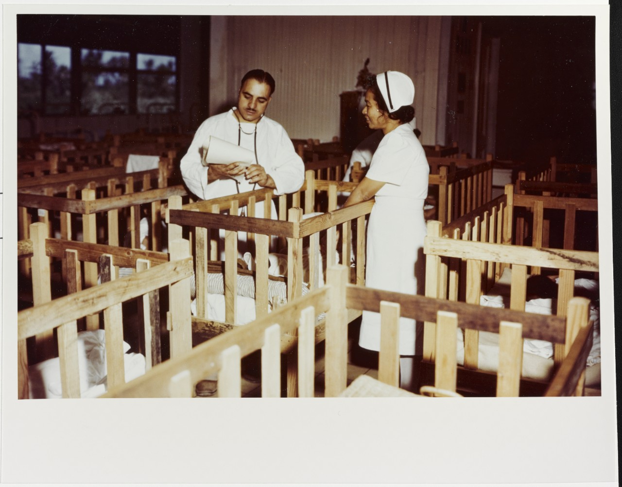 Lieutenant William B. Ruocco, USNR (MC) making the rounds in the children's ward in Agana, Guam in 1944-1945
