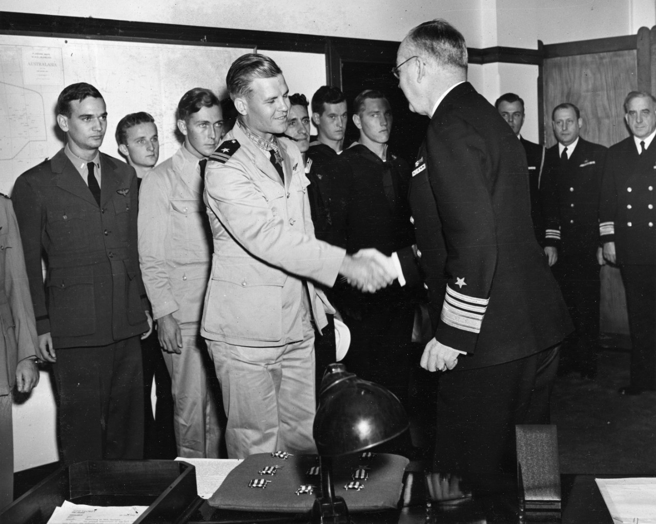 Vice Admiral Thomas C. Kinkaid, USN (right) (Commander, Seventh Fleet) and Lieutenant Nathan G. Gordon, USNR (left) shaking hands after Gordon was presented the Medal of Honor at Seventh Fleet Headquarters on 19 August 1944.