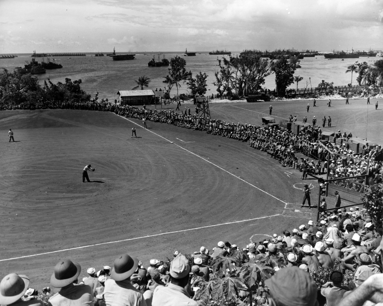 "A baseball exhibition game is held at ""Gab-Gab"" Fleet Recreation Area, Guam, July 1945. Note the close proximity of warships in the harbor. Courtesy FADM Nimitz."