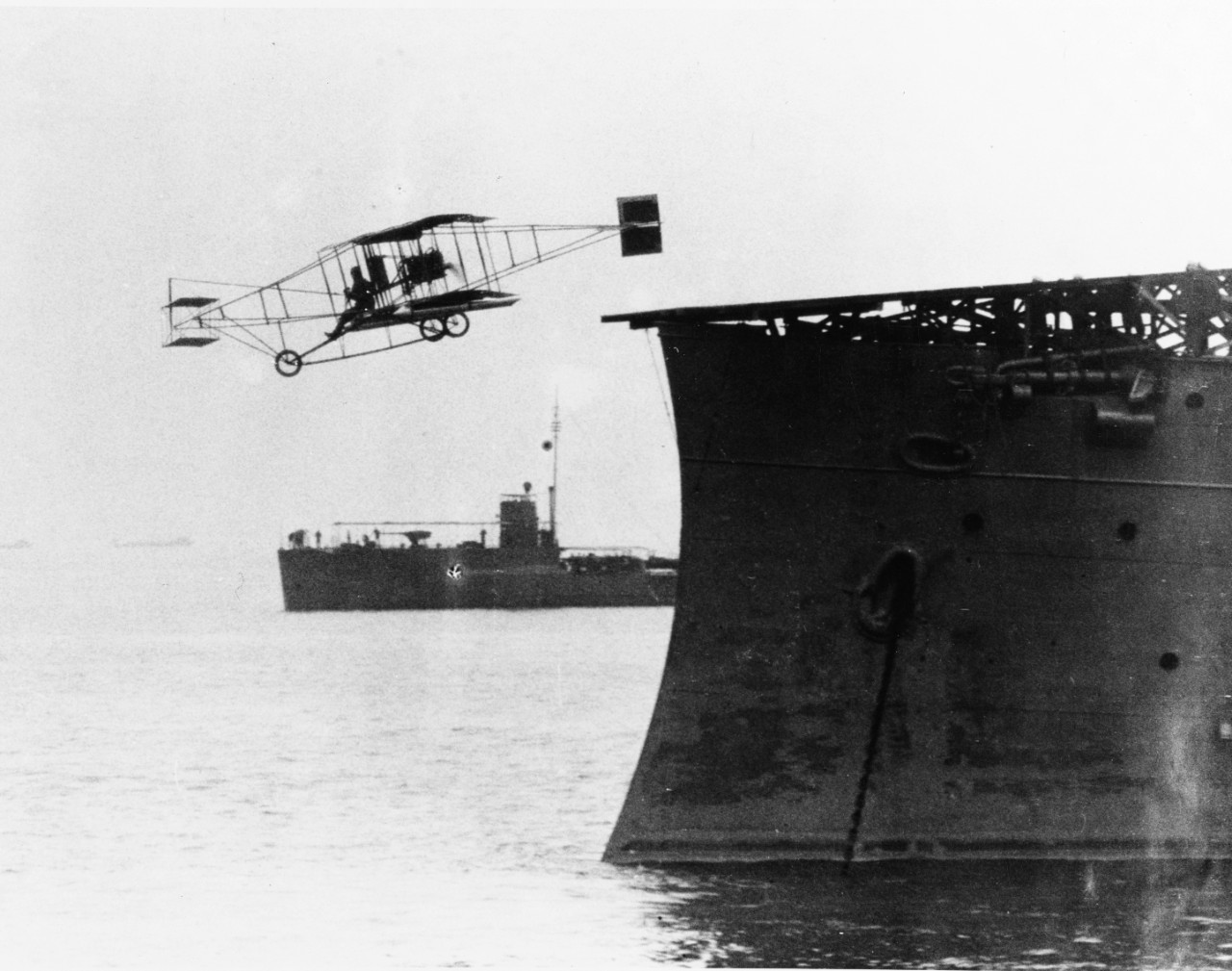 Eugene B. Ely flies his Curtiss pusher airplane from USS Birmingham (Scout Cruiser # 2), in Hampton Roads, Virginia, during the afternoon of 14 November 1910. USS Roe (Destroyer # 24), serving as plane guard, is visible in the background. Photograph from the Eugene B. Ely scrapbook collection, S-005.