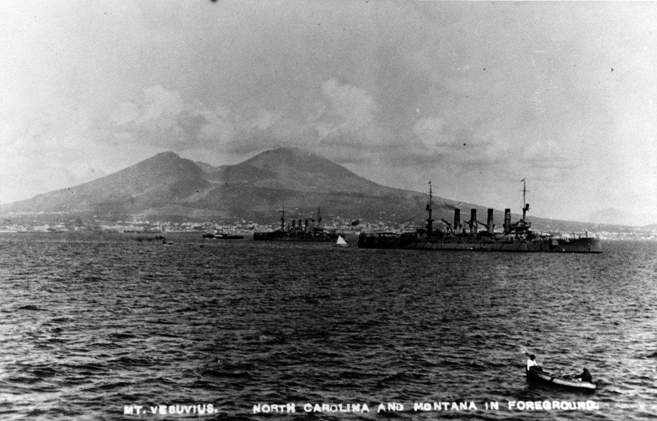 USS North Carolina (ACR-12) and USS Montana (ACR-13) in Naples harbor, Italy, with Mount Vesuvius in the distance, circa May-July 1909. Courtesy of Donald M. McPherson.