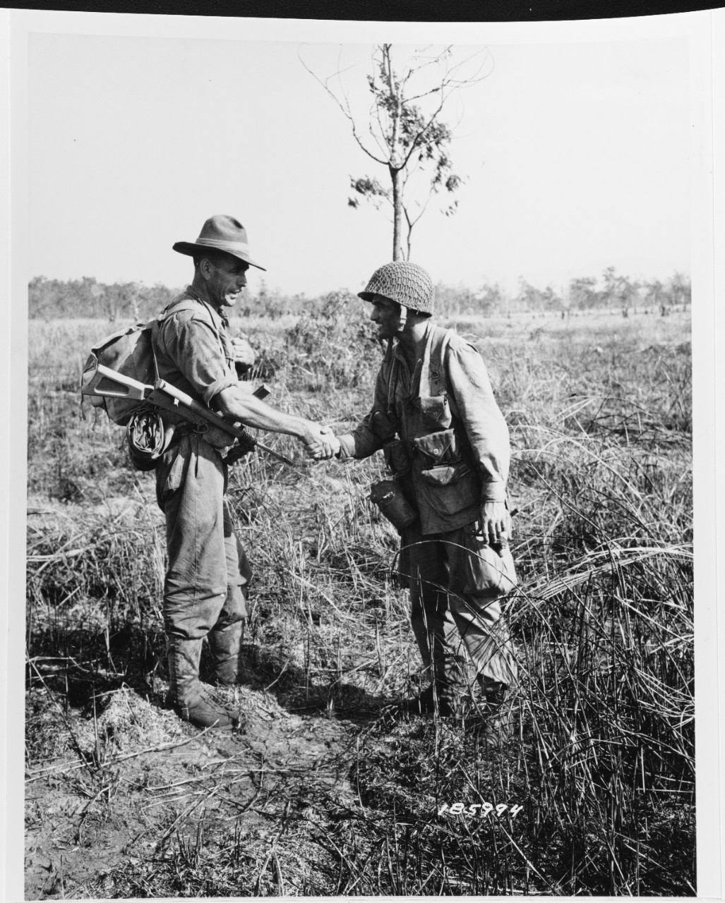 """SC 185994 Nadzab Airfield, near Lae, New Guinea. An Australian """"Digger"""" and  a U.S. Army Paratrooper meet at Nadzab on 6 September 1943."""