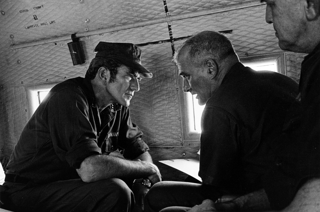 Admiral Elmo R. Zumwalt. Jr., USN, Chief of Naval Operations (left), and Rear Admiral Robert S. Salzer, USN, Commander Naval Forces Vietnam, discuss their recent visit to Nam Can Naval Base, Republic of Vietnam, as the fly to their next stop, May 1971. Official U.S. Navy Photograph.