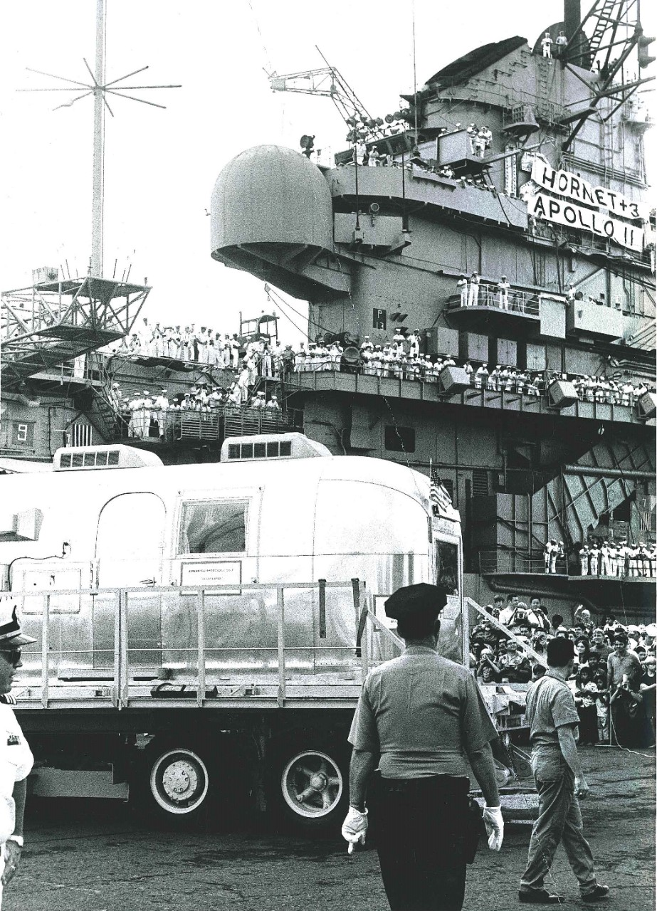 <p>The Mobile Quarantine Facility containing the Apollo 11 astronauts is&nbsp;offloaded from USS Hornet (CVS-12)&nbsp;at Pearl Harbor. One of the astronauts&nbsp;waves from&nbsp;the window.&nbsp;</p>