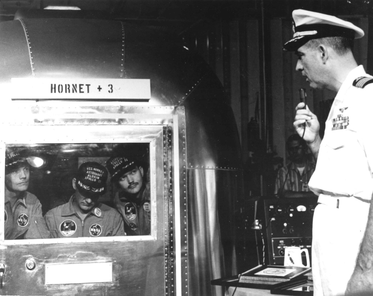<p>Captain Carl Seiberlich speaks with the Apollo 11 astronauts, who are inside the Mobile Quaratine Facility.</p>