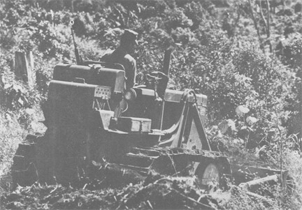 Image of Navy Seabee Clears a Site with His Bulldozer for a Missionary School in the Highlands of South Vietnam. Special SEABEE detachments Travel throughout South Vietnam building roads, constructing buildings and digging wells to assist the South Vietnamese civilians
