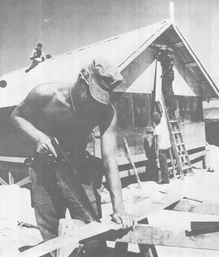 Image of Navy SEABEE Saws Wood as Other MCB-4 Men Work on New Living Quarters at Air Strip Being Constructed at Chu Lai, South Vietnam