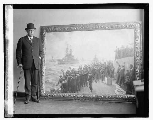 "Admiral Hugh Rodman, USN, standing with the painting by Bernard F. Gribble ""Arrival of the American Fleet"" at Scapa Flow, December 1917 on the occasion of its arrival in Washington, D.C. shortly before the photo was published 10 April 1923. National Photo Company Collection (Library of Congress), LC-DIG-npcc-08177 (digital file from original)."