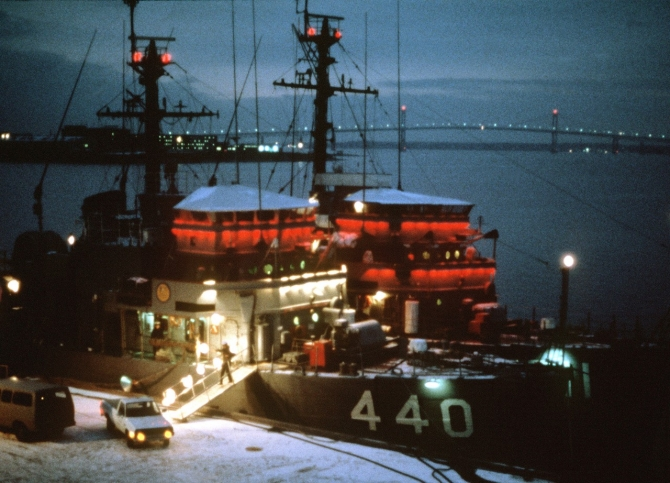 Exploit (left) and Affray are brightly illuminated to celebrate the season while moored at Newport, 1 December 1982. Snow covers the pier and the Mount Hope Bridge rises in the background. (JO2 Lance Johnson, Department of Defense Photograph 330-CFD-DN-ST-83-11429, Record Group 330 Records of the Office of the Secretary of Defense, 1921–2008, National Archives and Records Administration)
