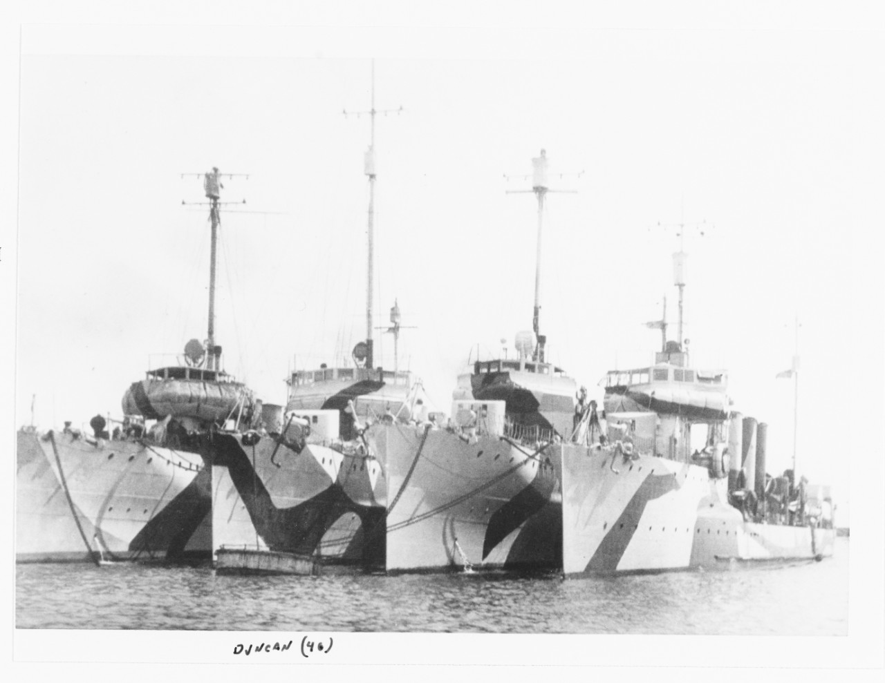 "Destroyers moored at Brest, France, circa 1918. The right-hand ship is probably Ammen, second from left is Duncan (Destroyer No. 46). Note variations in application of ""dazzle"" camouflage. (Naval History and Heritage Command Photograph NH 100434)"
