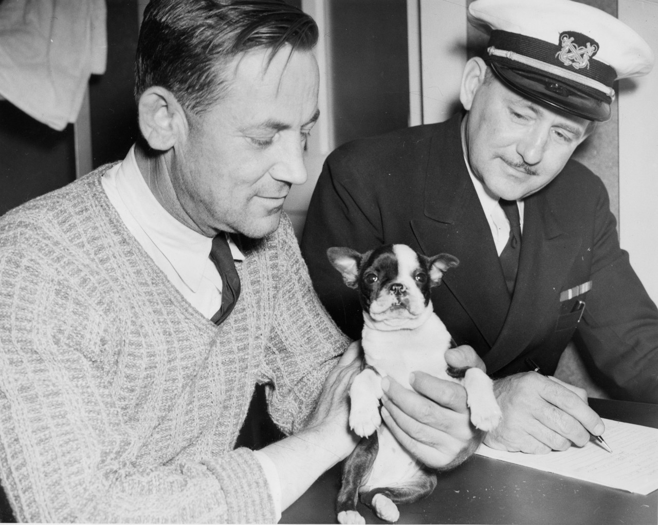 "Capt. George Fisk, Empire Thrush's master, holds ""Elizabeth,"" his 5-week old Boston Bulldog, during the debriefing of his ship's crew. (U.S. Navy Photograph 80-CF-105-4A-1, National Archives and Records Administration, Still Pictures Branch, College Park, Md.)"