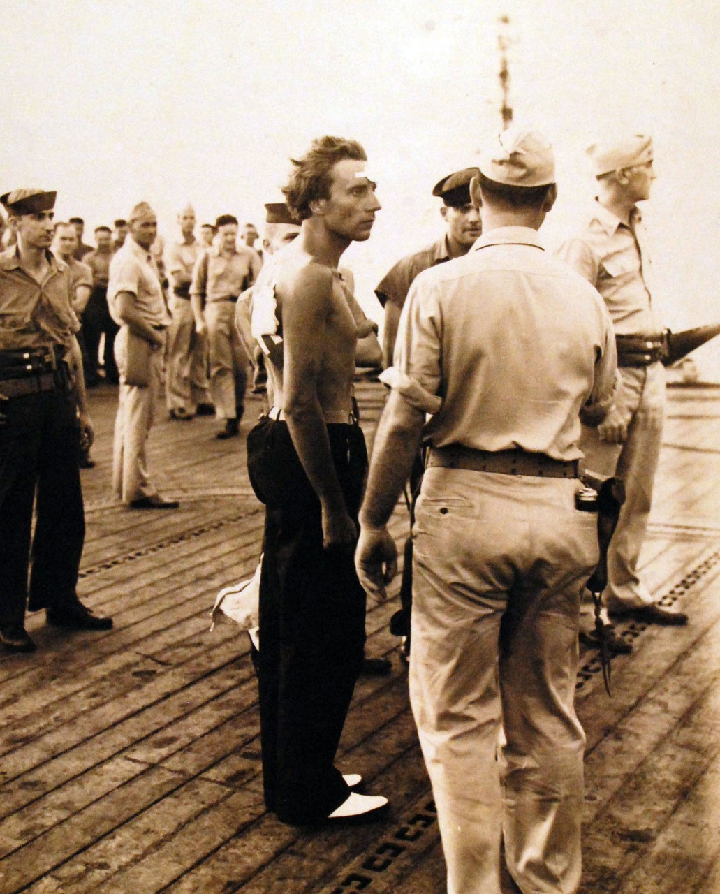 The Master-At-Arms and sailors, many armed, direct the German survivors as they gather on the flight deck of Core (CVE-13), 24 August 1943. Kapitänleutnant August Maus, U-185's commanding officer, stands wounded but defiant in the center. (Unattributed U.S. Navy Photograph 80-G-77199, National Archives and Records Administration, Still Pictures Branch, College Park, Md.)