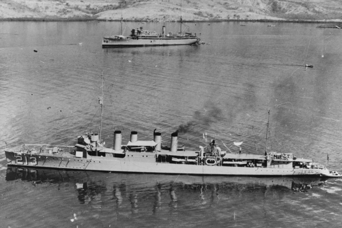 Barker puts in to Gonaives, Haiti, March 1928. She has steam up in a single boiler, a seaman hangs wash on one of the lines just aft of amidships, and a boat is tethered to her stern. Other vessels come and go in the busy harbor as the fleet carries out training. (Unattributed U.S. Navy Photograph 80-G-421850, National Archives and Records Administration, Still Pictures Branch, College Park, Md.)
