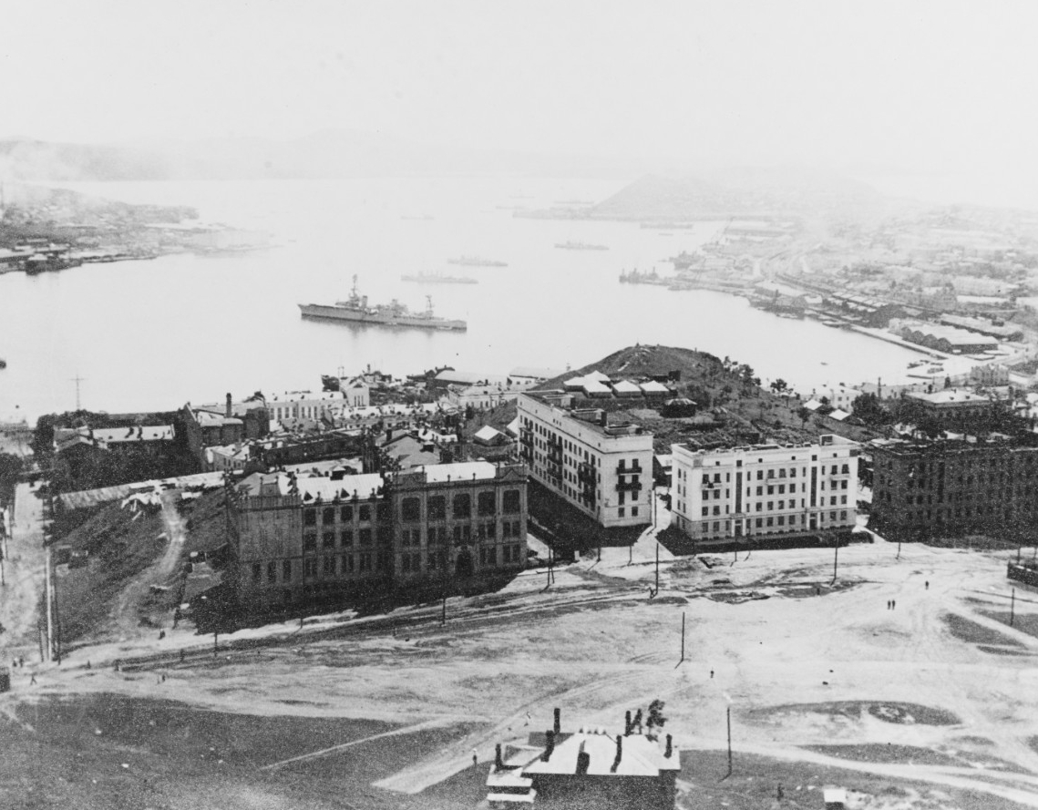 "Despite recent clashes between Chinese and Japanese troops at the Marco Polo Bridge, U.S. ships carry out a rare visit to the Soviet port of Vladivostok, 26 July–1 August 1937. They narrowly avoid a typhoon while en route, and their visit marks the first by U.S. naval vessels since the Navy closes its radio station in the port in 1922. Adm. Harry E. Yarnell, Commander Asiatic Fleet, breaks his flag in heavy cruiser Augusta (CA-31), to the left of center, and later summarizes the rare visit: ""The visit of this force evidently has meant a great deal to these people,"" as the Soviets lavishly entertain the Americans. The stern of one the destroyers can be seen to the left of the picture while the other three are in line broadside to each other and Augusta. The four destroyers are: Alden (DD-211), Barker, Paul Jones (DD-230), and Whipple (DD-217). (Courtesy of Rear Adm. James P. Walker, Naval History and Heritage Command Photograph NH 77820)."