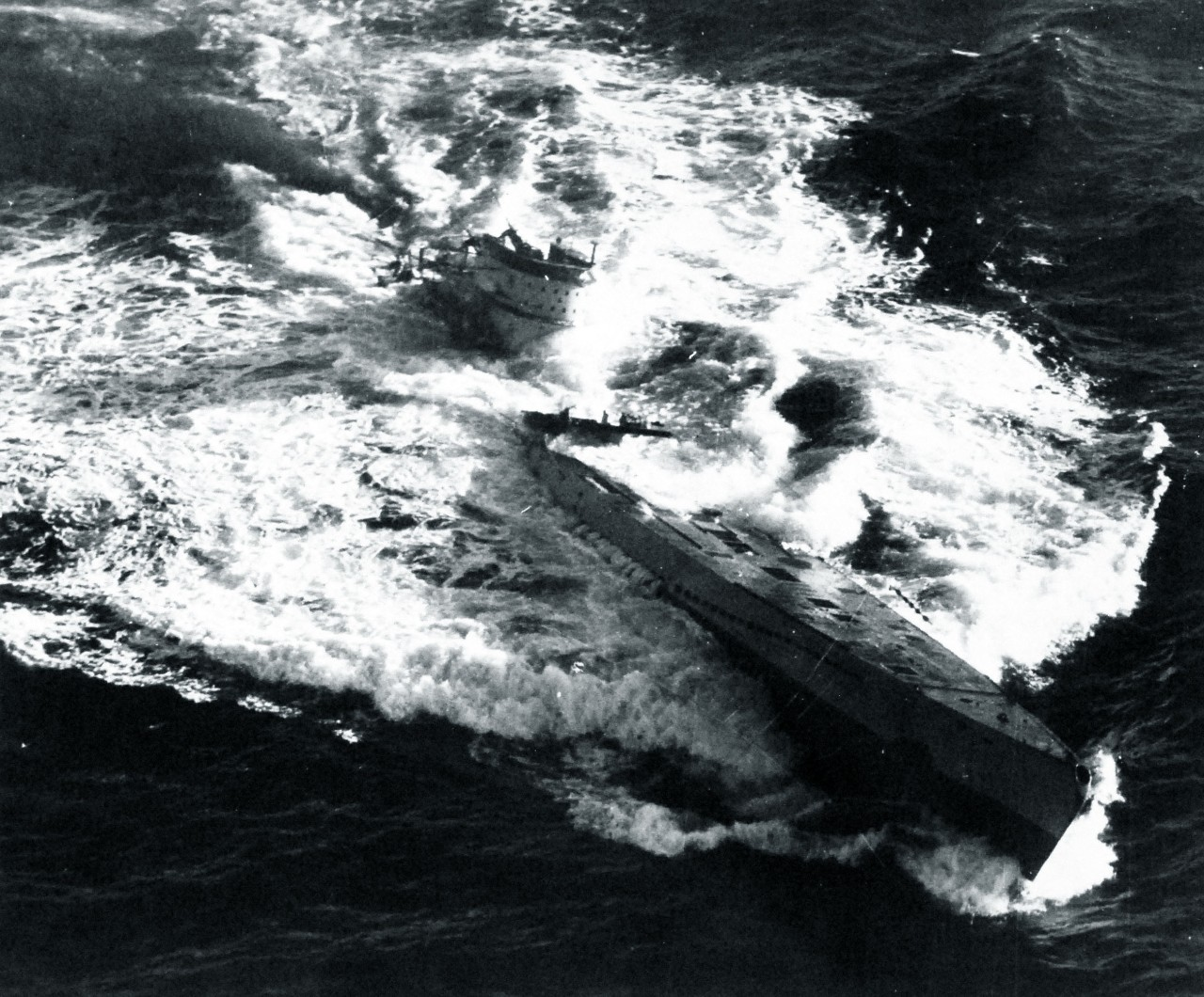 U-185 sinks, 24 August 1943. Note that the bomb that hits forward all but blasts her 4.1-inch deck gun over the side, that the U-boat lists slightly to port, and that she has lost trim by the stern. (Unattributed U.S. Navy Photograph 80-G-77196, National Archives and Records Administration, Still Pictures Branch, College Park, Md.)