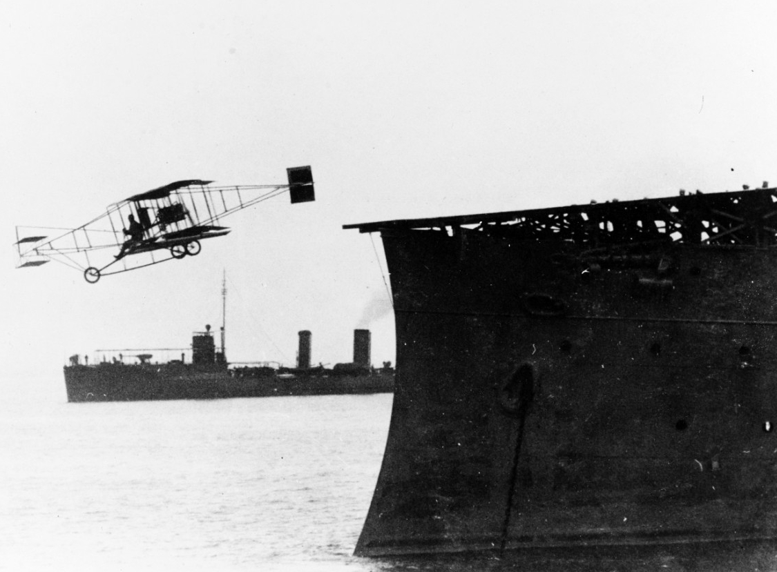 Ely flies his plane off the deck of Birmingham, 14 November 1910. Roe (Destroyer No. 24) is among the ships that stand by during the historic event and is visible in the background. (Naval History and Heritage Command Photograph NH 76511)
