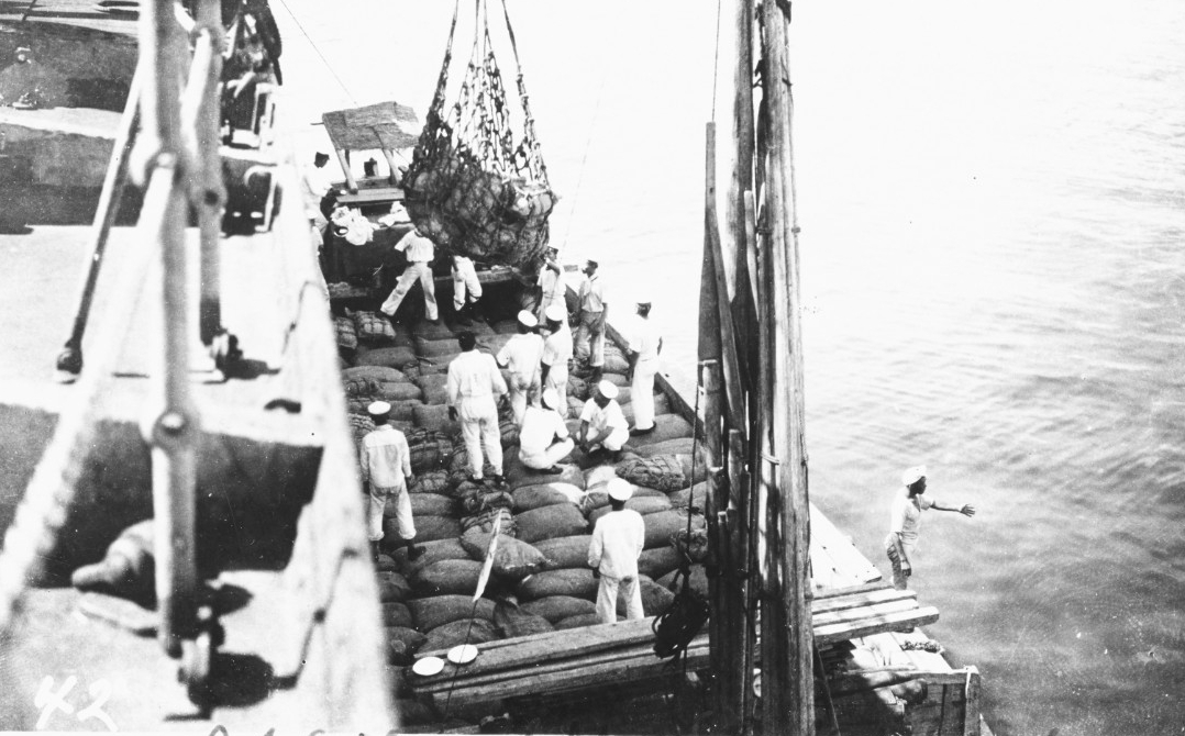 Japanese sailors help unload Black Hawk after her arrival in Tokyo Bay with relief supplies for victims of the great earthquake of September 1923. (Naval History and Heritage Command Photograph NH 100371)