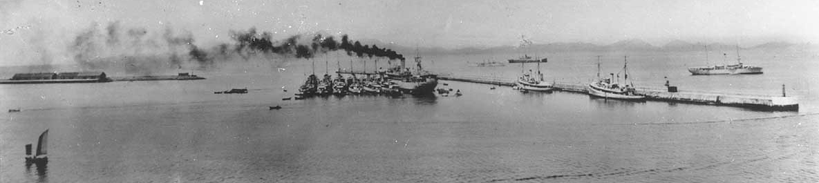 Panoramic photograph of Chefoo harbor during the 1930s. Black Hawk lies moored in the center, with the destroyers of Destroyer Division (DesDiv) 14 alongside. Two U.S. Navy minesweepers are by the breakwater and a gunboat is anchored off shore, at the extreme right. (Naval History and Heritage Command Photograph NH 90041)