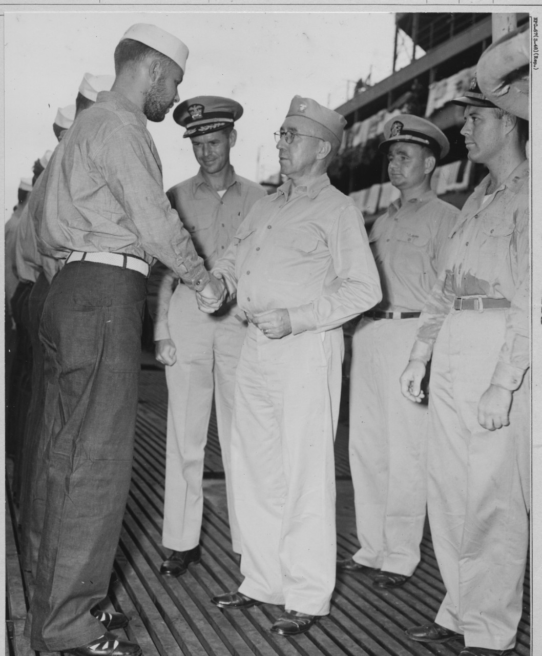 While Cmdr. John F. Davidson looks on approvingly, Rear Adm. Fife exchanges pleasantries with a bearded member of Blackfish's crew on the occasion of the men being awarded their Submarine Combat Insignias, 23 December 1943. Note bedding airing on the lifelines of the tender in the background. (U.S. Navy Photograph 80-G-394433, National Archives and Records Administration, Still Pictures Division, College Park, Md.)