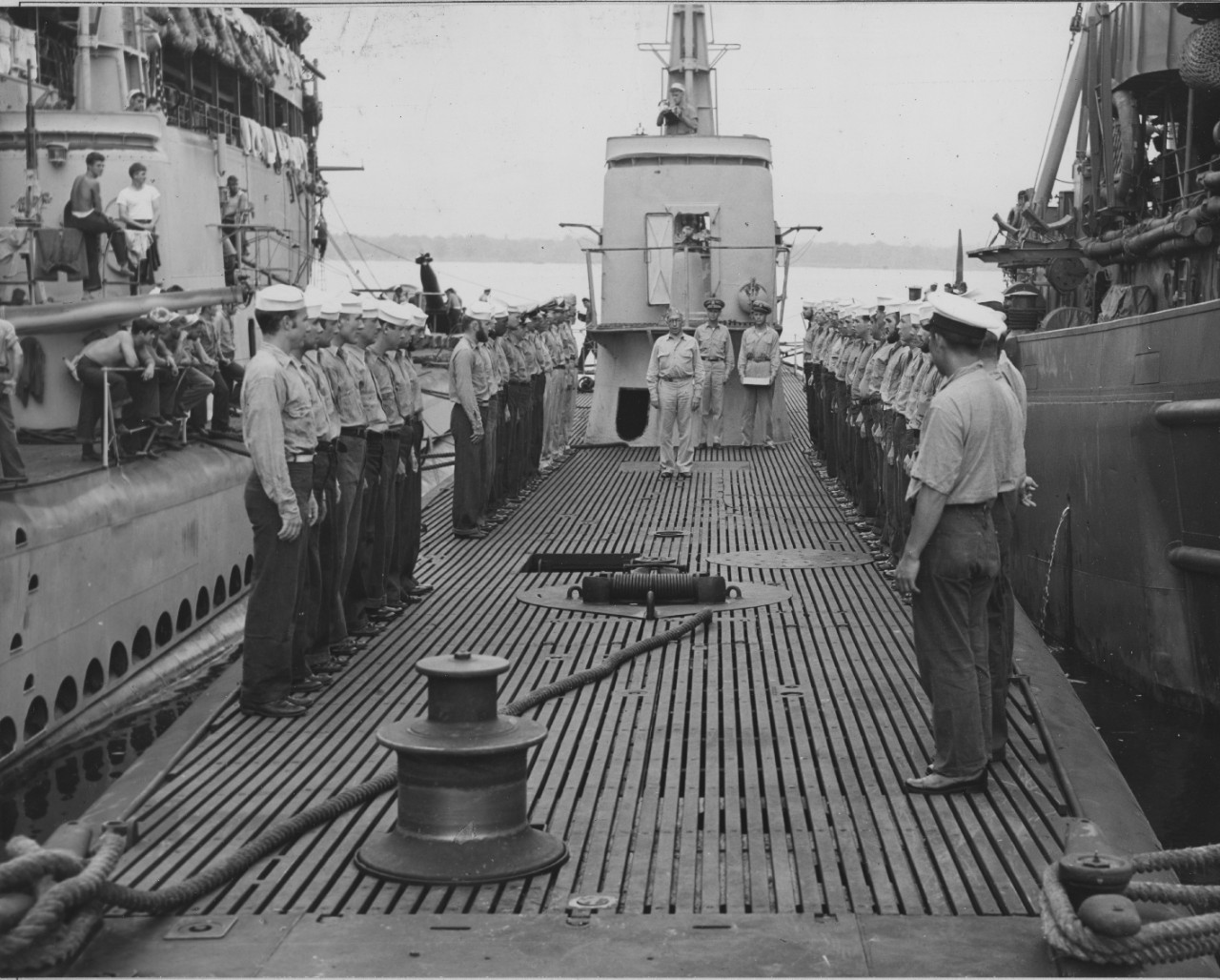 Rear Adm. James Fife addresses Blackfish's crew, standing at attention, as he provided them with their Submarine Combat Insignias, 23 December 1943. Note how the sailors on board the boat moored alongside (L) display a more casual onlooker's stance. Also note photographer readying his camera on Blackfish's bridge. (U.S. Navy Photograph 80-G-394429, National Archives and Records Administration, Still Pictures Division, College Park, Md.)