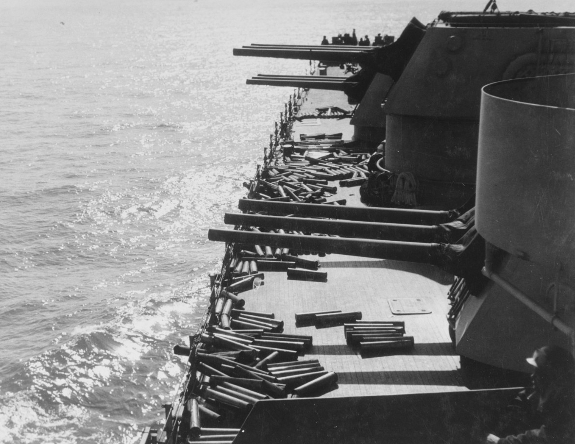 Empty shell casings litter Brooklyn's deck near the ship's forward 6-inch turrets as she blasts German and Italian soldiers during the landings at Licata, Sicily, 10 July 1943. (U.S. Navy Photograph 80-G-42522, National Archives and Records Administration, Still Pictures Division, College Park, Md.)