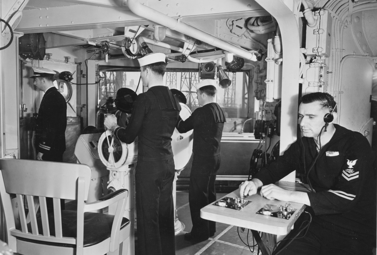 A scene of Brooklyn's pilothouse, looking to starboard, as the ship completes her construction at the New York Navy Yard, 18 January 1938. Note the men at the helm and engine order telegraph (left), and the radioman at the communications table (right). (Naval History and Heritage Command Photograph NH 56626)