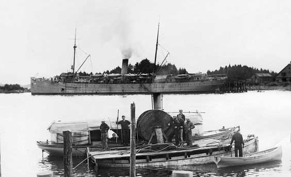 Boats from Buffalo preparing to lay a communications cable at Sitka, Alaska, in fall 1914, during the Alaskan Radio Expedition. A steam launch from the ship is alongside an improvised pontoon carrying the cable reel. (Naval History and Heritage Command Photograph NH 105453)