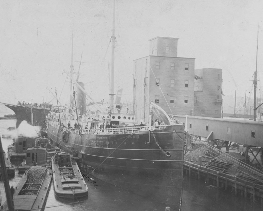 Nictheroy, formerly El Cid, fitting out for Brazilian Navy service in November 1893 at the Morgan Iron Works, New York, N.Y. Her former name, El Cid, has been painted out on the bow, but the ship still wears the rest of her mercantile paint scheme. (Naval History and Heritage Command Photograph NH 105941)