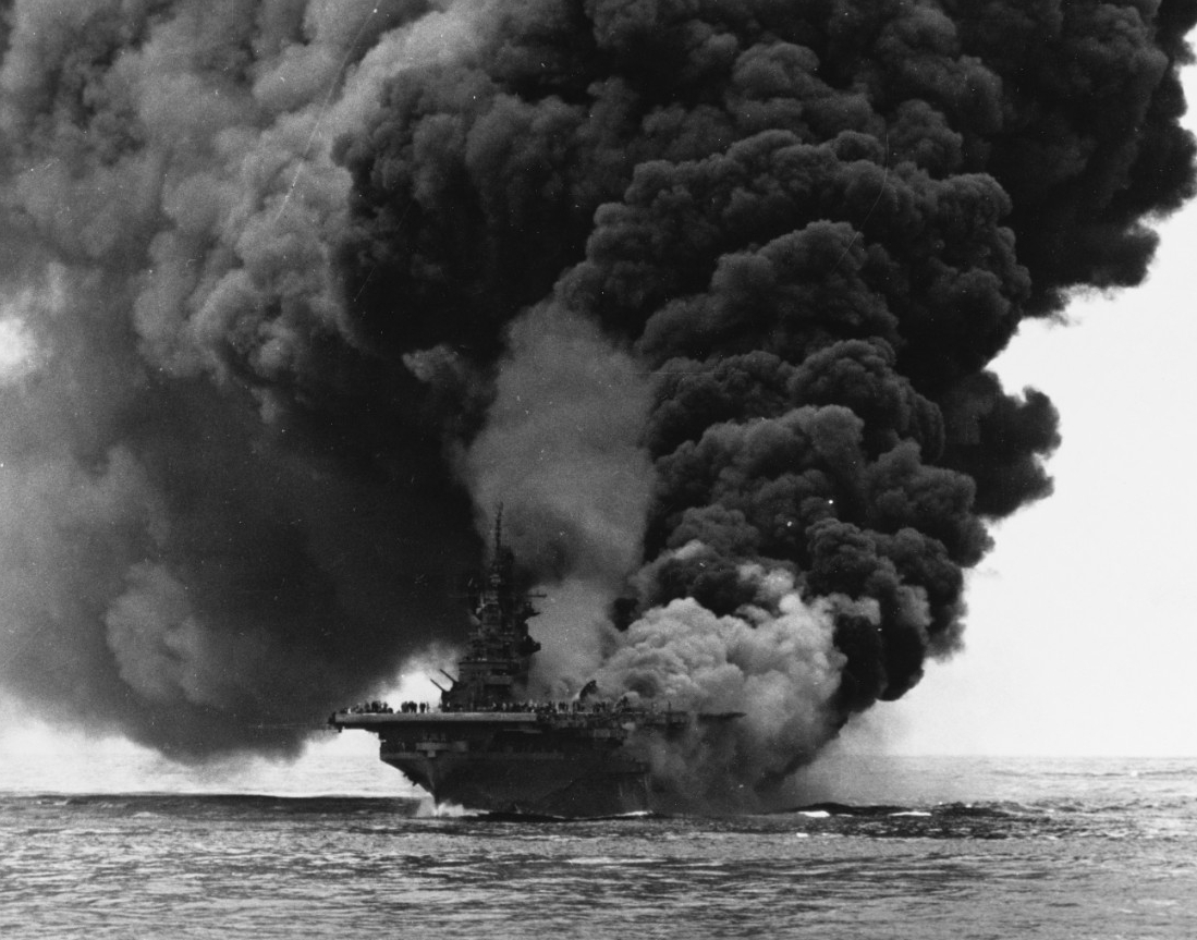 Burning and with heavy smoke pouring from the aft end of her flight deck as well as the hangar deck, Bunker Hill fights for her life some 60 miles off the shore of Okinawa after two kamikazes plunged into her, 11 May 1945. This photo is taken from Bataan (CVL-29). (U.S. Navy Photograph 80-G-274266, National Archives and Records Administration, Still Pictures Division, College Park, Md.)