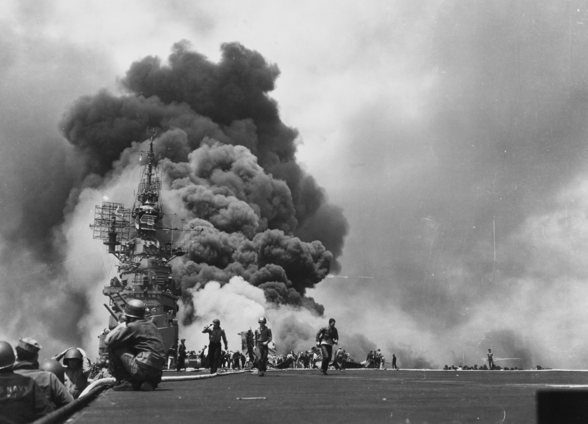 The scene on Bunker Hill's flight deck looking aft, while her crew fights fires caused by the two kamikaze attacks off Okinawa on 11 May 1945. This iconic image from World War II appears on the RCA Victor recording of the orchestral suite Victory at Sea in the early 1950s. (U.S. Navy Photograph 80-G-323712, National Archives and Records Administration, Still Pictures Division, College Park, Md.)
