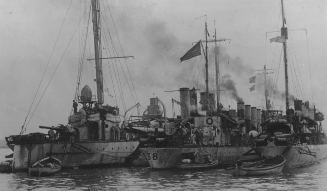 Destroyers Little (Destroyer No. 79), Jarvis (Destroyer No. 38), and Burrows, lying (L-R) in the inner harbor ready for convoy service, Brest, France, 27 October 1918, in this image captured by a Pvt. Barnes of the U.S. Army Signal Corps. Note weathered paintwork and details of depth charge tracks on board all three ships. Little carries her identification number in low-contrast camouflage paint, the configuration of her stern requiring the numerals to be painted on each side, whereas Jarvis' identification number is painted across her rounded stern just beneath the name JARVIS. Also note Burrows' badly damaged starboard propeller guard (R). (U.S. Army Signal Corps Photograph 111-SC-30973, National Archives and Records Administration, Still Pictures Branch, College Park, Md.)
