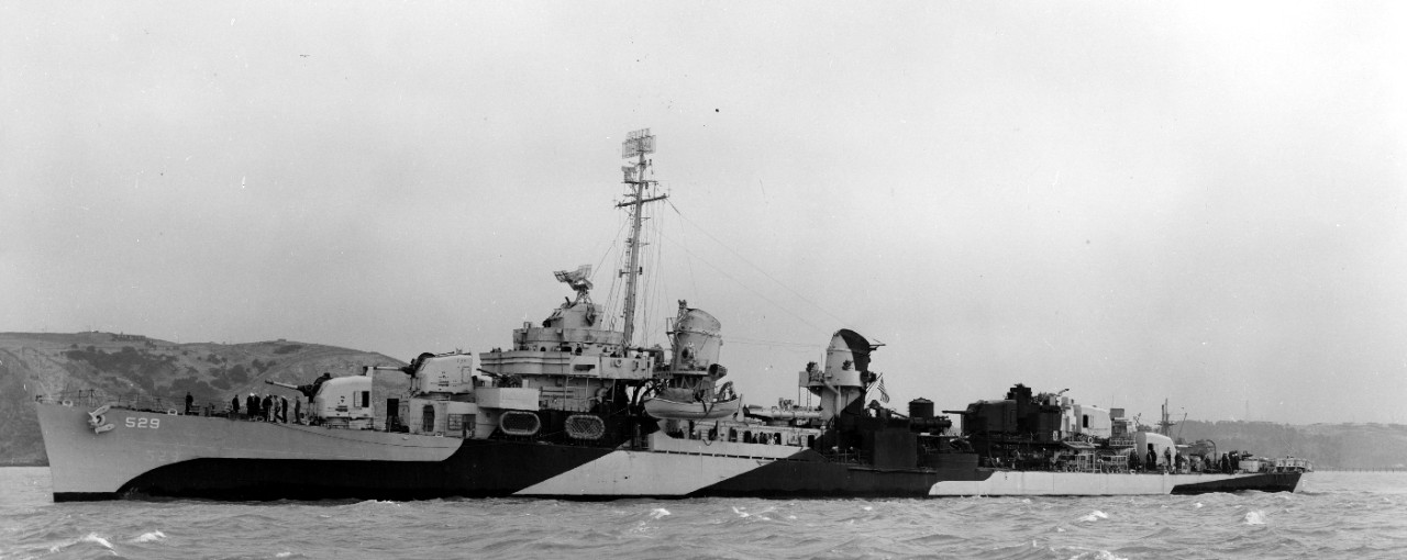 Underway near Mare Island, Bush, painted in Ocean Gray (5-O) and Black, stands down the channel, 11 June 1944. Note the different bridge configuration from that with which she had been completed, and the heavier armament forward, with twin-mount 40-millimeter Bofors guns replacing the single 20-millimeters. Also note that her identification number has been repainted in a different style, and higher, and in a more forward, position on the hull, closer to the bow, and that the repainted number is still faintly visible. (U.S. Navy Bureau of Ships Photograph BS-67647, National Archives and Records Administration, Still Pictures Division, College Park, Md.)