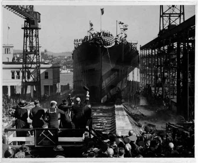 California slides down the way during her launching ceremony at the Mare Island Navy Yard on 20 November 1919. The group standing on the christening stand to the lower left of the photograph includes Mrs. Barbara S. Zane, daughter of the state's Governor William D. Stephens and the ship's sponsor (on the left), a Navy captain lifting his hat to the battleship, a motion picture cameraman, and a bugler. (Naval History and Heritage Command Photograph NH 55016)