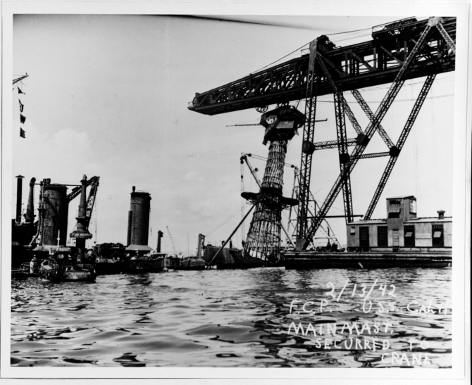 "A floating crane removes the ship's battered ""basket"" mainmast during her salvaging, 13 February 1942. (Courtesy of Vice Adm. Homer N. Wallin, 1975 (Naval History and Heritage Command Photograph NH 55038)"
