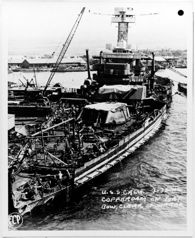 Workmen repair the ship after she is raised and moored at Pearl Harbor, 30 March 1942. Note the cofferdam installed along her port bow and the forward turrets with their guns removed. (Courtesy of Vice Adm. Homer N. Wallin, U.S. Navy Photograph NH 55036, Photographic Section, Naval History and Heritage Command)