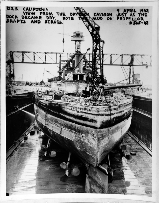 California enters Dry Dock No. 2 at Pearl Harbor for repairs, 9 April 1942. Shipyard workers have just drained the water from the dry dock, exposing the mud on her propeller shafts and struts. (Unattributed U.S. Navy Photograph NH 64483, Photographic Section, Naval History and Heritage Command)