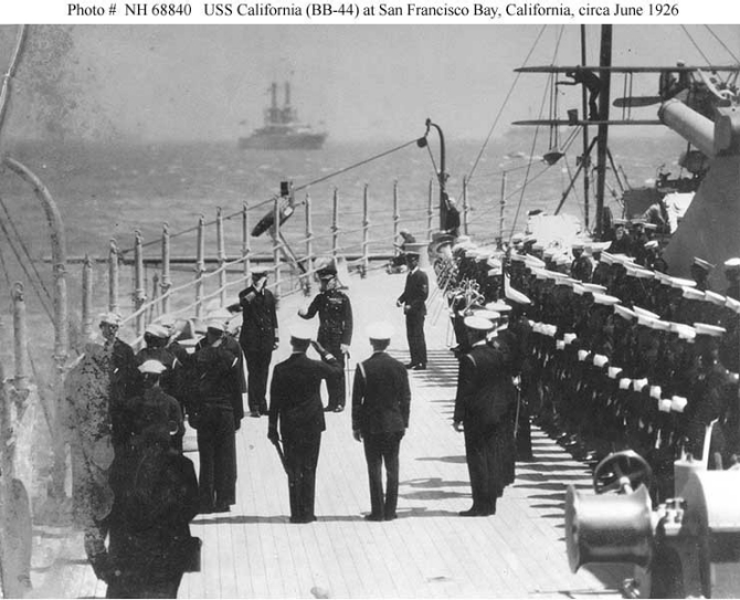 California and 67 other ships of the Battle Force, its screen, and auxiliaries steam into San Francisco Bay for a brief visit, 18 June 1926. Capt. William H. Standley, California's commanding officer, exchanges salutes with Brig. Gen. Smedley D. Butler, USMC (both of whom stand just left of the center of the picture). Note the marine guard and ship's band to the right. (Courtesy of the San Francisco Maritime Museum) (Naval History and Heritage Command Photograph NH 68840)