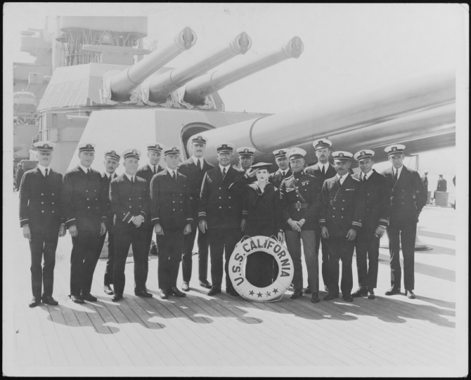 Officers of the ship's company pose with Dorothy Devore, a silent film star and comedian on board the ship at San Pedro, Calif., 1925. Devore (22 June 1899–10 September 1976) was cast in 36 films during a career spanning two decades. Lt. Abraham DeSomer stands third from the right. Note the caps in the barrels of the triple 14-inch guns, and the overall cleanliness of the ship, the deck of which has likely been holystoned for the event. (Collection of Lt. Cmdr. Abraham DeSomer, donated by Lt. Col. Russell DeSomer, USAFR, 1975) (Naval History and Heritage Command Photograph NH 103839)