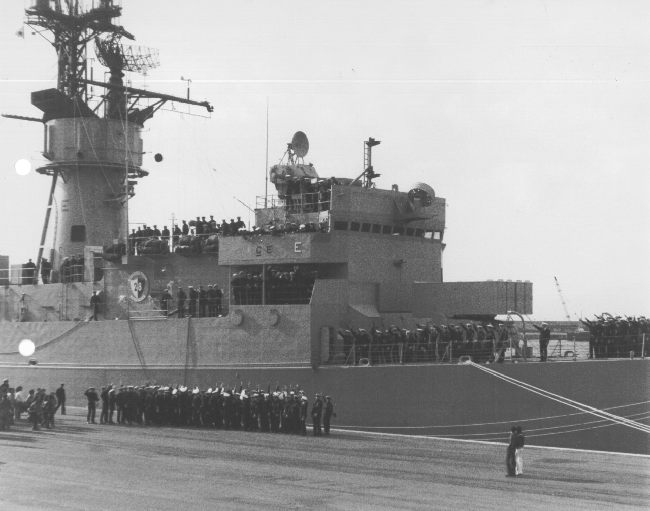 "Capodanno's crew celebrates winning the Battle Efficiency Award by painting an ""E"" on the ship's bridge wings, mack, and gun mount. (Capodanno (DE-1093), Ship's History, Naval History and Heritage Command)"