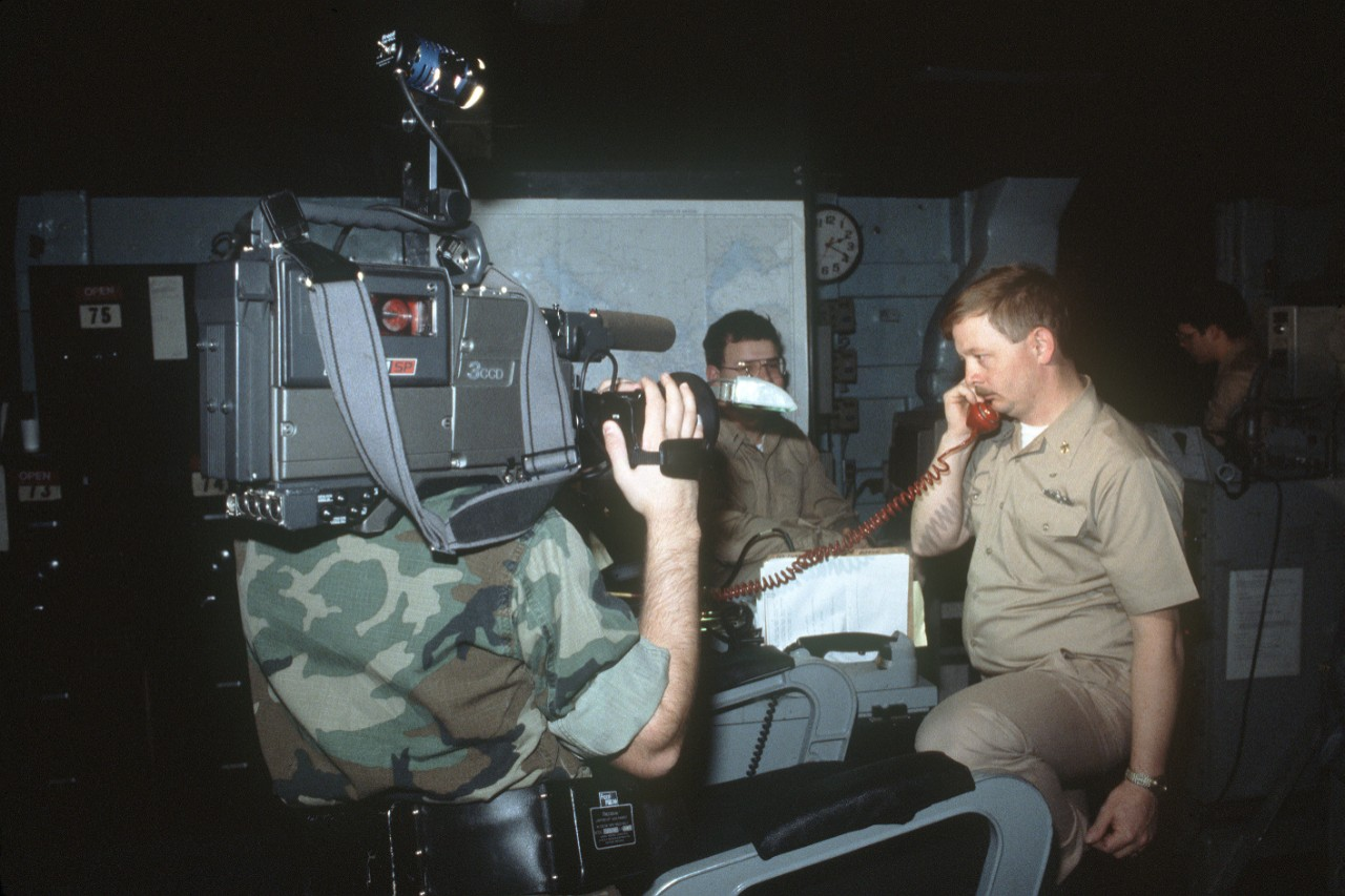 A cameraman films a man on board Capodanno participating in radio interoperability tests between U.S. and Soviet naval forces, 6 December 1989. (U.S. Navy Photograph by JO3 William G. Davis III, Defense Imagery Management Operations Center, Ft. Meade, Md., DN-ST-90-03887)