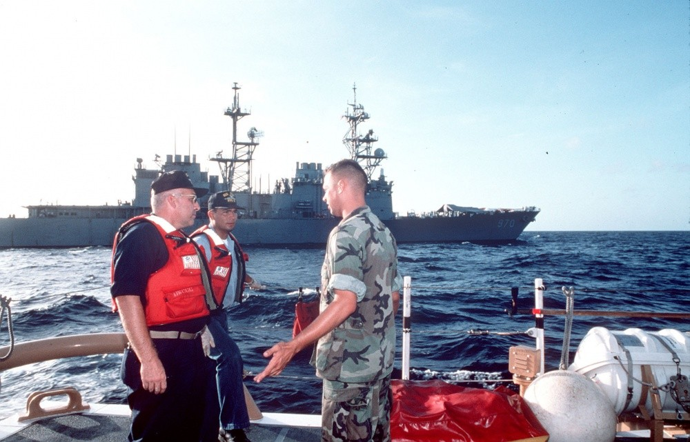 Members of a U.S. Coast Guard law enforcement detachment (LEDET) and a Navy sailor discuss plans during Operation Able Vigil off the coast of Cuba; Caron in background. Note shelter set up on the ship's bow, 19 September 1994. (U.S. Coast Guard Photograph 1080582, Defense Visual Information Distribution Service)
