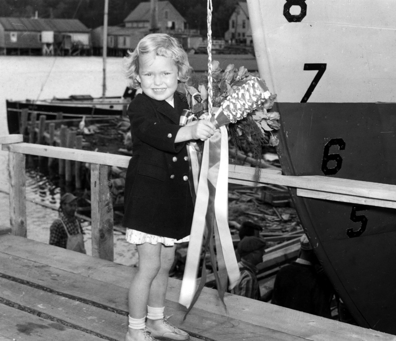 Little Joanne Witherell holds what appears to be an appropriately sized bottle of Great Western champagne as she prepares to christen Chachalaca – up to that time the largest vessel ever constructed by the Bristol Yacht Building Co. -- on 11 June 1941. (Chachalaca (AMc-41) Ships Name and Sponsor Files, History and Archives Division, Naval History and Heritage Command)