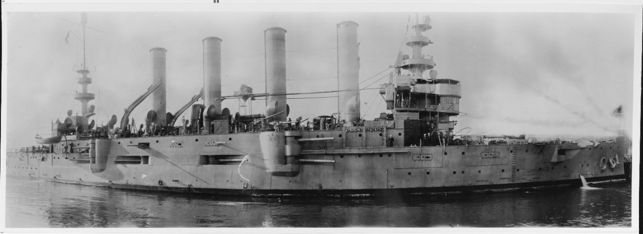 "A photograph of Charleston, circa 1917. The panoramic view emphasizes the ship's diverse armament including some of her 6-inch guns in their ""box battery"", mounted on the gun deck within the upper casemate, with separating splinter bulkheads, the forward and after pairs of this arrangement sighted in sponsons. In addition, some of the 3-inch rapid firing guns mounted outboard on the main deck are also visible. (Naval History and Heritage Command Photograph NH 95243)"