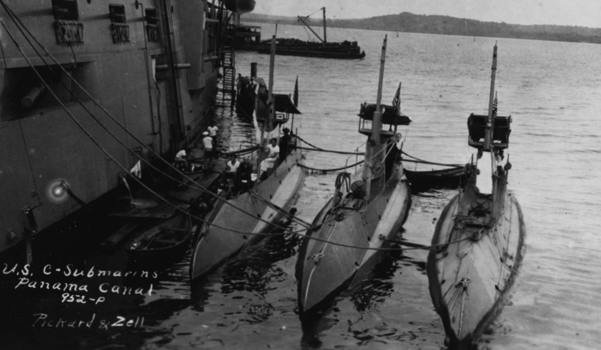 Charleston tends (left–right) C-5 (Submarine No. 16), C-2 (Submarine No. 13), and C-3 (Submarine No. 14) while operating in the Panama Canal Zone, circa 1916–1917. Note the sailors washing clothes on the float between the cruiser and her charges, and the small rowboat. (Naval History and Heritage Command Photograph NH 100941)