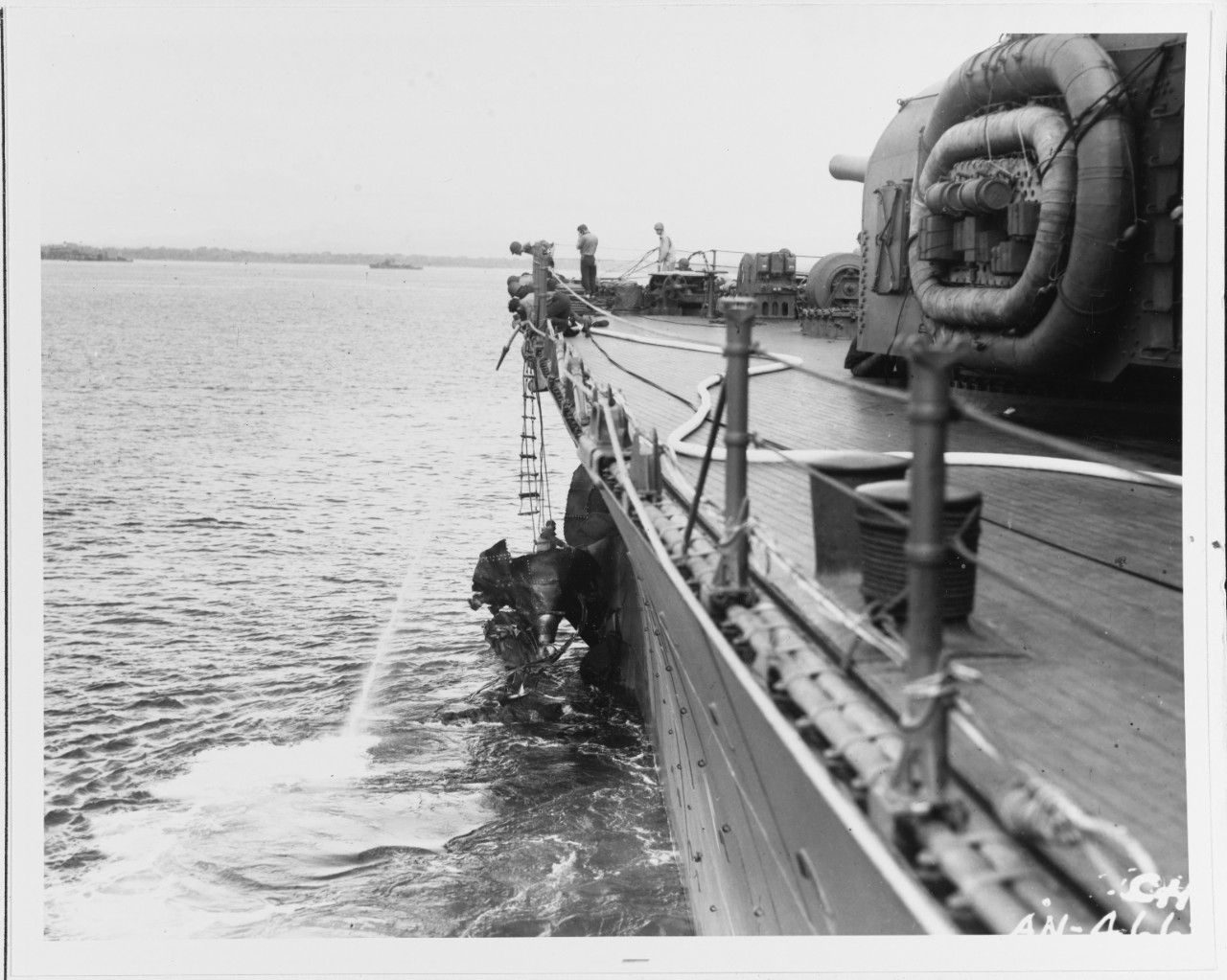 Chicago crewmen cut away damaged plating from where the Japanese torpedo struck to enable the damaged cruiser to get underway following the Battle of Savo Island, 9 August 1942. The photographer's glass captures the view looking forward along the port side, and the 8-inch guns of Turret I on the upper right. Note the life rafts hung on the side of the turret and the destroyers in the distance. (U.S. Navy Photograph 80-G-34685, National Archives and Records Administration, Still Pictures Branch, College Park, Md.)
