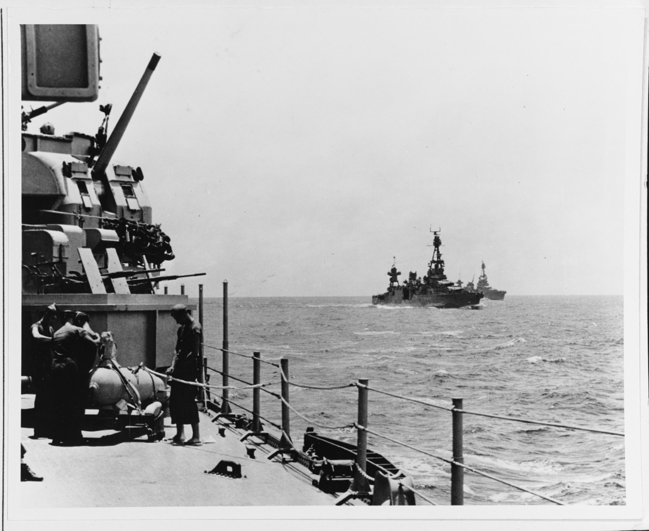 A photographer on board Wichita captures a shot of Chicago (right center) and Louisville (in the distance) as they steam to fight the Japanese during the Battle of Rennell Island, 29 January 1943. Note some of Wichita's 5-inch and 20 millimeter guns behind the men working on a paravane. (U.S. Navy Photograph 80-G-38824, National Archives and Records Administration, Still Pictures Branch, College Park, Md.)