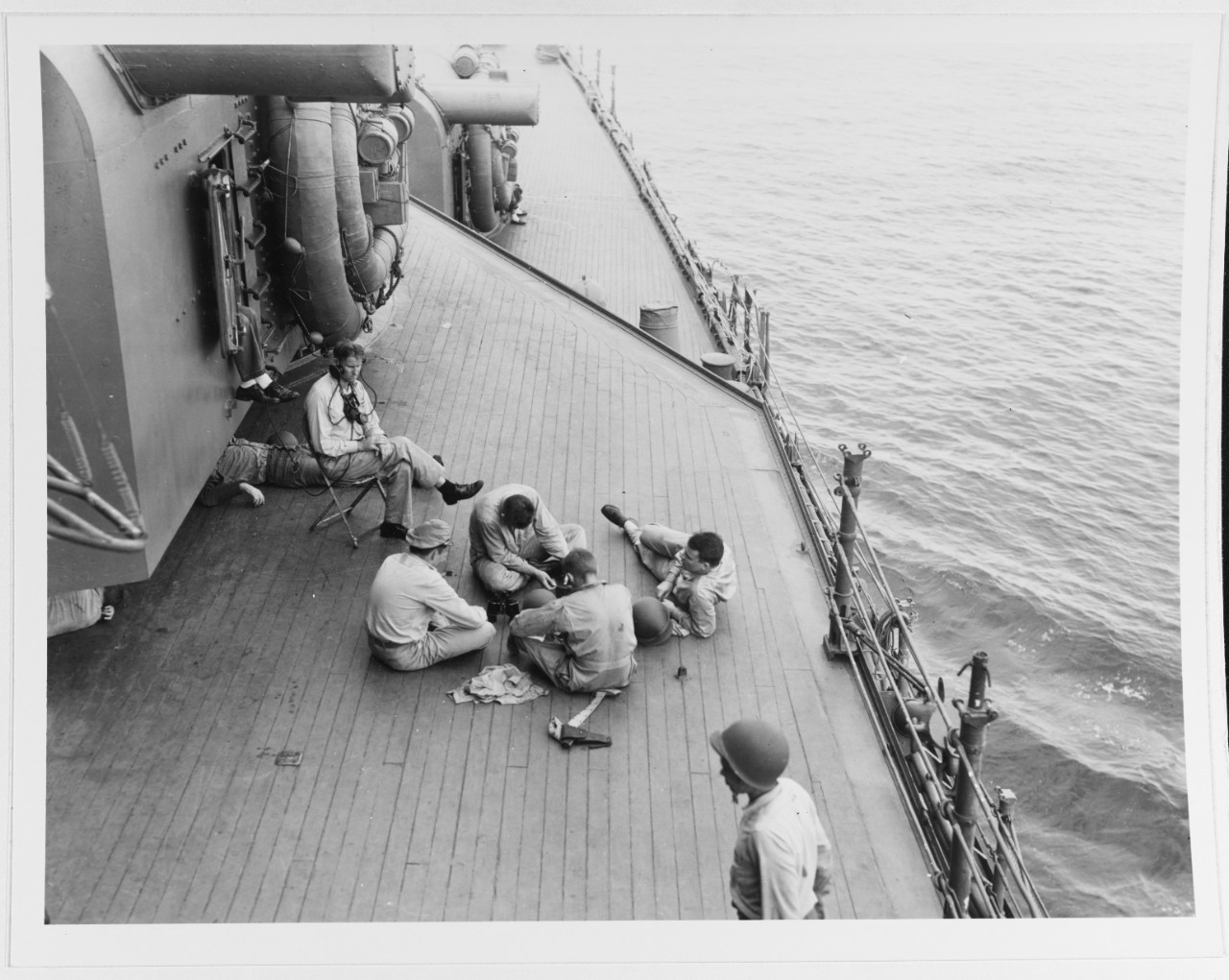 Men rest on Chicago's deck beside 8-inch turret No. II, 9 August 1942. The view looks forward on the starboard side, as the ship appears to be underway. Note the lookout in the chair wearing the headphones, the .45 caliber M1911 pistol in the holster on deck, the lifelines cleared away, the life rafts carried on the turret side, and the wooden decking. (U.S. Navy Photograph 80-G-13490, National Archives and Records Administration, Still Pictures Branch, College Park, Md.)