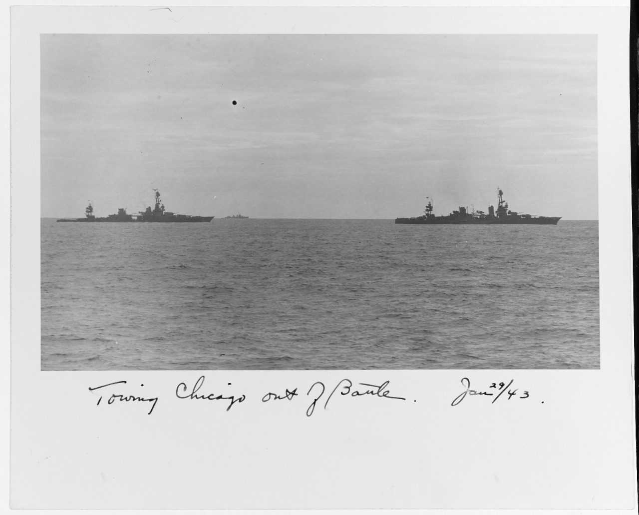 Chicago (left) slowly emerges from the battle under tow of Louisville on the morning of 30 January 1943. A tug, most likely Navajo (AT-64), steams alongside Louisville. (Collection of Vice Adm. Robert C. Giffen, Naval History and Heritage Command Photograph NH 94681)